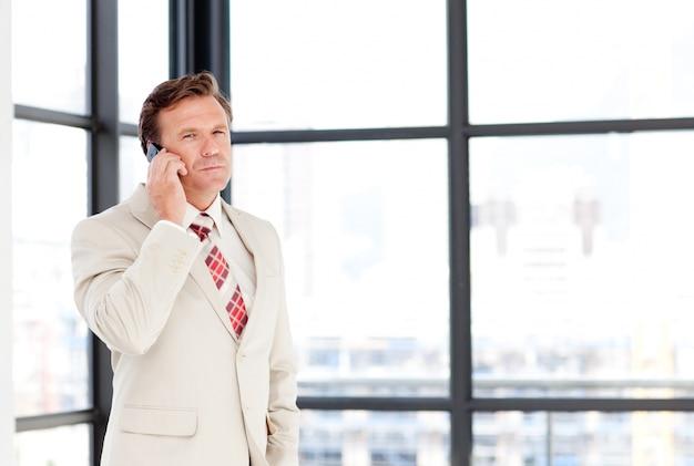 Uomo d'affari maggiore sul telefono con copia-spazio