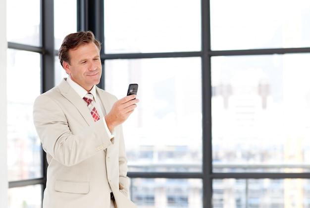 Imprenditore senior inviando un sms con copia-spazio