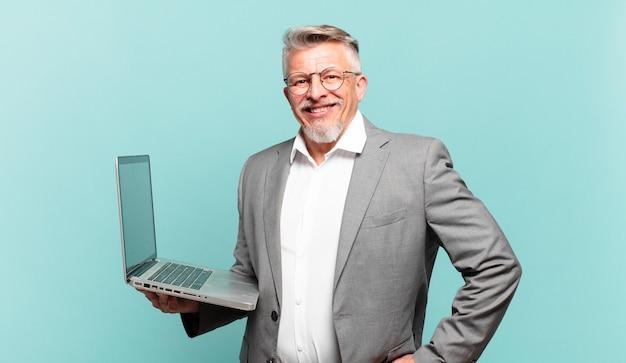 Uomo d'affari senior che sorride felicemente con una mano sull'anca e un atteggiamento fiducioso, positivo, orgoglioso e amichevole