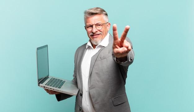 Uomo d'affari anziano che sorride e sembra felice, spensierato e positivo, indicando vittoria o pace con una mano