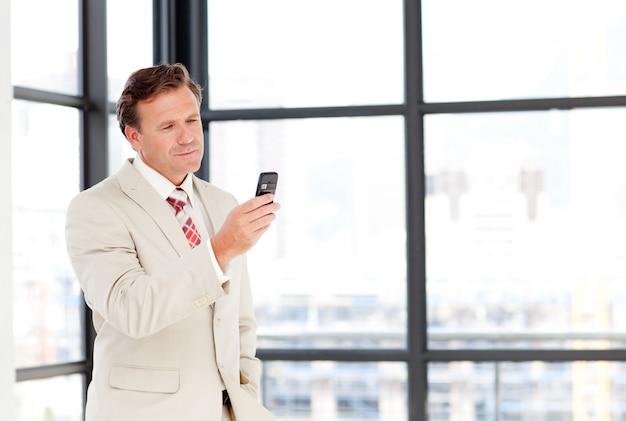 Uomo d'affari maggiore che manda un sms con copia-spazio