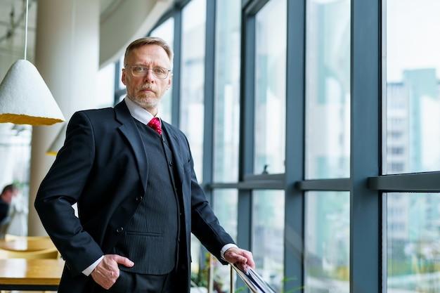 L'uomo d'affari senior indossa un abito moderno e una camicia bianca. grande finestra con vista sulla città. foto dal lato.