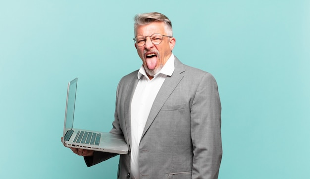Uomo d'affari senior con atteggiamento allegro, spensierato, ribelle, scherzando e tirando fuori la lingua, divertendosi