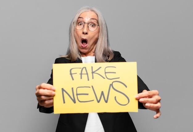 Donna d'affari senior con banner di notizie false