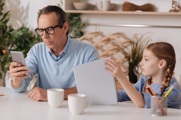 Uomo d'affari concentrato occupato anziano che utilizza gadget a casa e ignora la nipote mentre lavora e invia sms