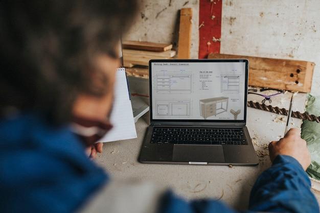 Carpentiere senior che scrive sul suo taccuino con il computer portatile sulla scrivania concetto di piccola impresa
