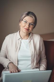 Senior caucasica imprenditrice con capelli biondi e occhiali da vista lavorando da casa al computer portatile