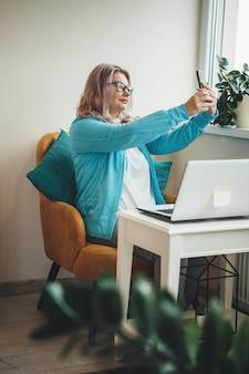 Senior imprenditrice caucasica con gli occhiali facendo un selfie seduto in poltrona e utilizzando un computer portatile