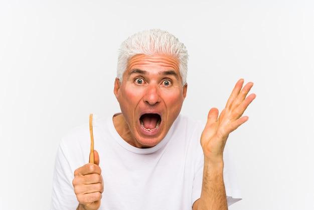 L'uomo caucasico senior che giudica uno spazzolino da denti ha isolato la celebrazione della vittoria o del successo