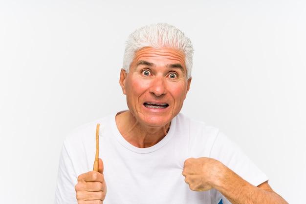 L'uomo caucasico senior che tiene uno spazzolino da denti ha sorpreso indicare se stesso