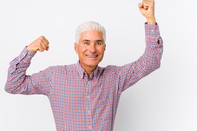 L'uomo caucasico senior isolato che celebra un giorno speciale, salta e alza le braccia con energia.