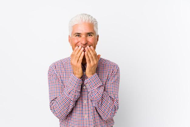 L'uomo caucasico senior ha isolato la risata di qualcosa, coprendo la bocca di mani.