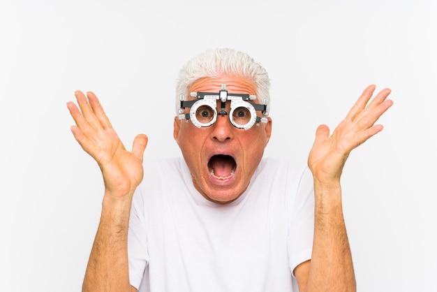 Uomo caucasico senior che indossa un telaio di prova all'ottico optometrista per celebrare una vittoria o un successo