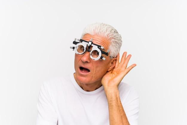 Uomo caucasico senior che indossa un telaio di prova all'ottico optometrista cercando di ascoltare un pettegolezzo.