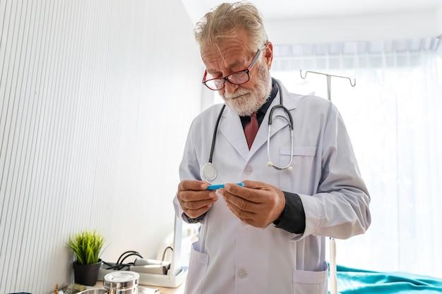 I professionisti caucasici senior aggiustano la tenuta con il termometro per controllo della febbre in un'infezione nella stanza di ospedale.