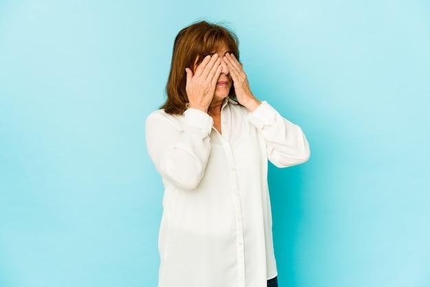 Donna caucasica senior isolata che copre gli occhi impauriti con le mani.