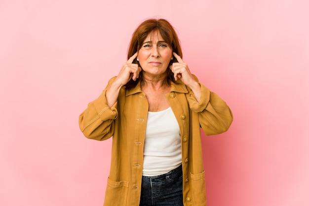 Senior donna caucasica isolata che copre le orecchie con le dita, stressata e disperata da un ambiente rumoroso.