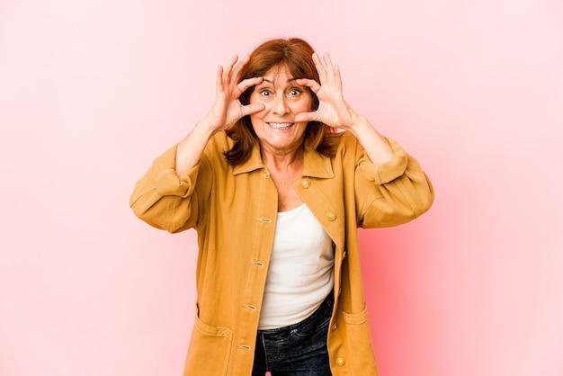 Senior donna caucasica isolata tenendo gli occhi aperti per trovare un'opportunità di successo.