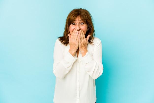 Senior donna caucasica isolata ridendo di qualcosa, coprendo la bocca con le mani.