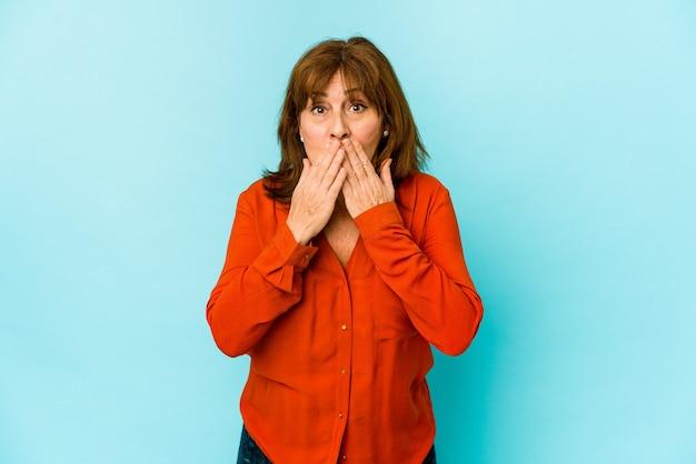 Senior donna caucasica isolata scioccata che copre la bocca con le mani.