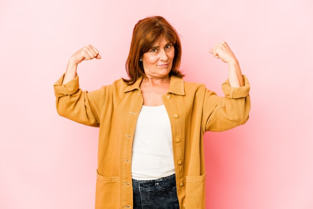 Senior donna caucasica isolata mostrando gesto di forza con le braccia, simbolo del potere femminile