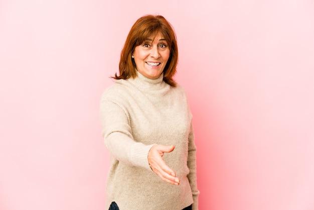 Senior donna caucasica isolata allungando la mano alla telecamera nel gesto di saluto.