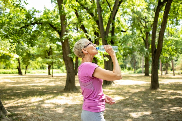 Senior donna caucasica prendendo una pausa e bere acqua dopo un lungo allenamento in natura.
