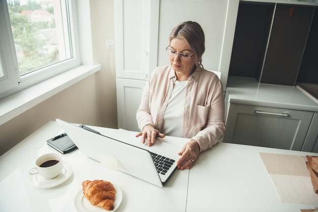 Senior donna caucasica che lavora in remoto al laptop da casa mentre beve un caffè con croissant