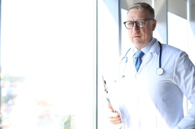 Capo medico senior in abito bianco con stetoscopio.