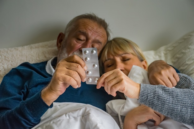 Coppia senior sul letto e le mani in possesso di farmaci