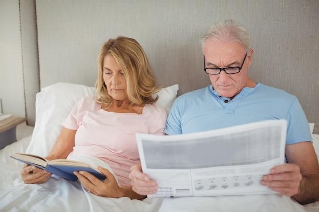 Coppia senior sul letto, leggere il giornale e il libro