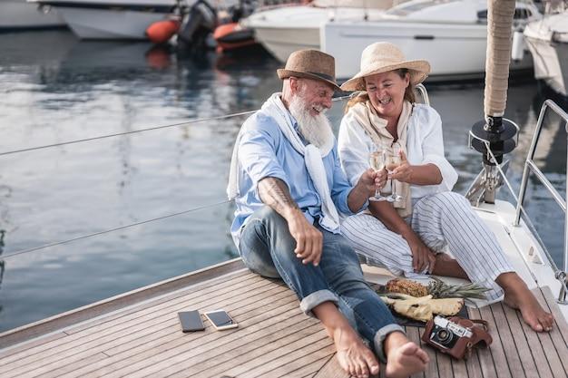 Coppia senior tifo con champagne in barca a vela durante le vacanze estive - focus sui volti