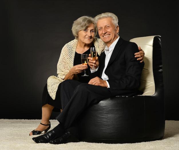 Coppia senior che beve champagne seduta in poltrona nera