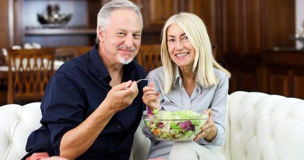 Coppie maggiori che mangiano un'insalata