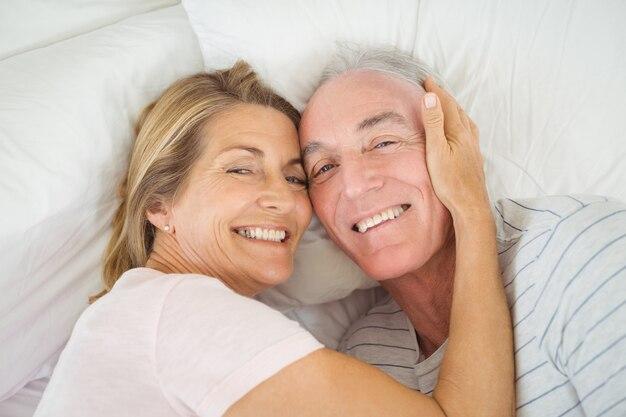 Coppia senior abbracciando sul letto