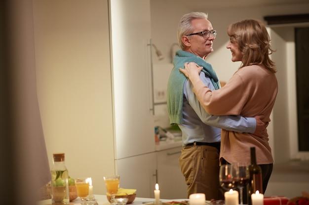 Coppia senior abbracciati e balli durante una cena romantica