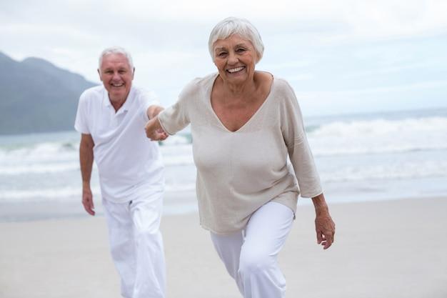 Coppie senior divertendosi insieme alla spiaggia