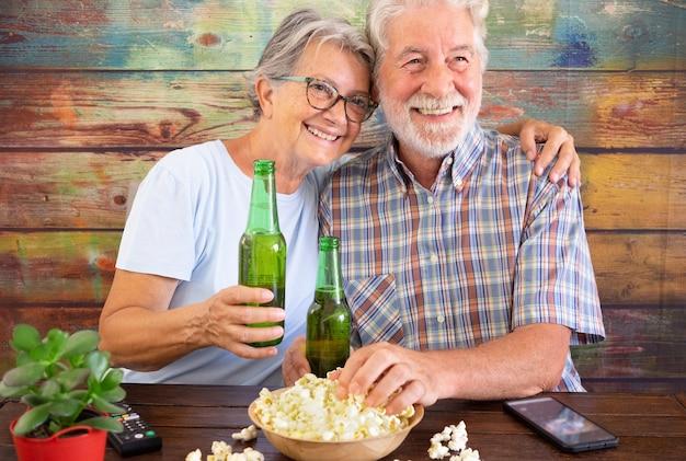 Coppia senior divertirsi guardando una partita di calcio in tv, bere birra e mangiare popcorn. sfondo in legno