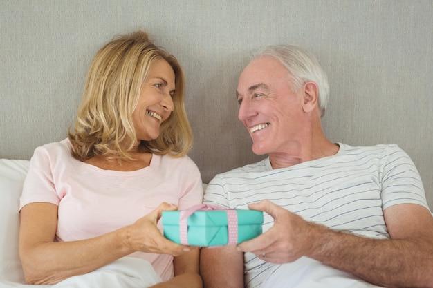 Coppia senior azienda confezione regalo sul letto