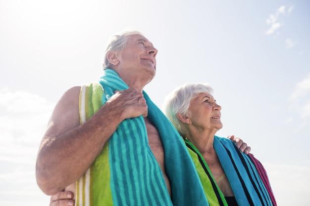 Coppia senior in possesso di un asciugamano intorno al collo