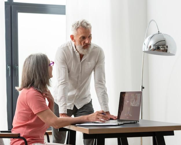 Coppia senior a casa utilizzando il computer portatile