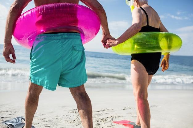 Coppia senior in anello gonfiabile e pinna che cammina verso il mare