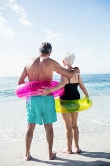 Coppia senior in anello gonfiabile in piedi sulla spiaggia