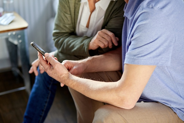 La coppia senior farà la videochiamata sul telefono con la famiglia, la conversazione online. distanza sociale, famiglia in casa, moderne tecnologie. concentrarsi sulle mani