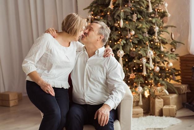 Coppia senior baciare accanto al loro albero di natale a casa in soggiorno