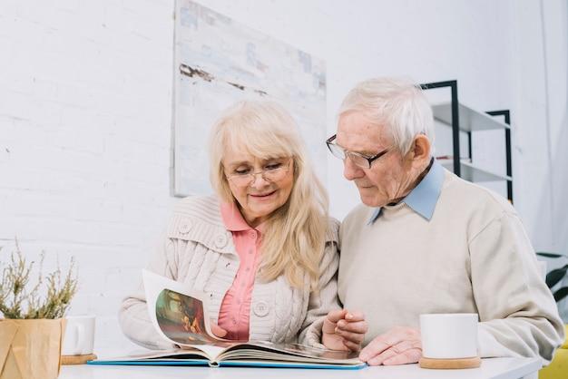 Coppia senior guardando album fotografico