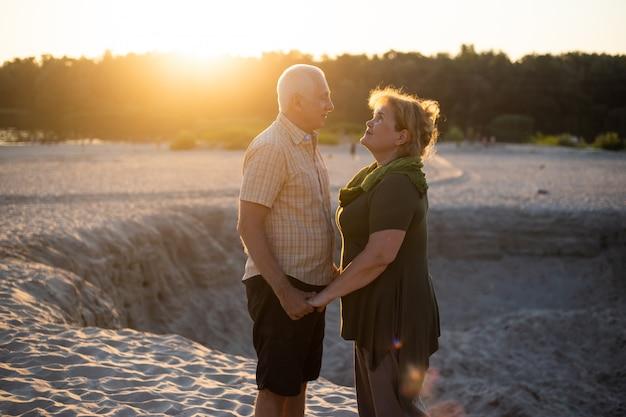 Coppie senior nell'amore che baciano insieme sul tramonto di estate