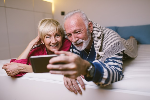 Coppia senior sdraiata sul letto e guardando qualcosa al tablet insieme.