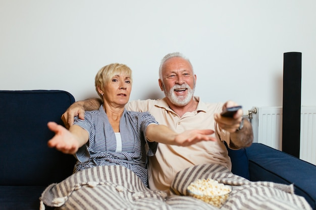 Coppia senior sdraiata sul letto e guardare la tv insieme.