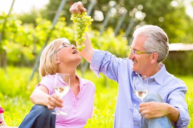 Coppia senior di uomo e donna che hanno picnic sul prato estivo bevendo vino in vigna, vizia la moglie con l'uva